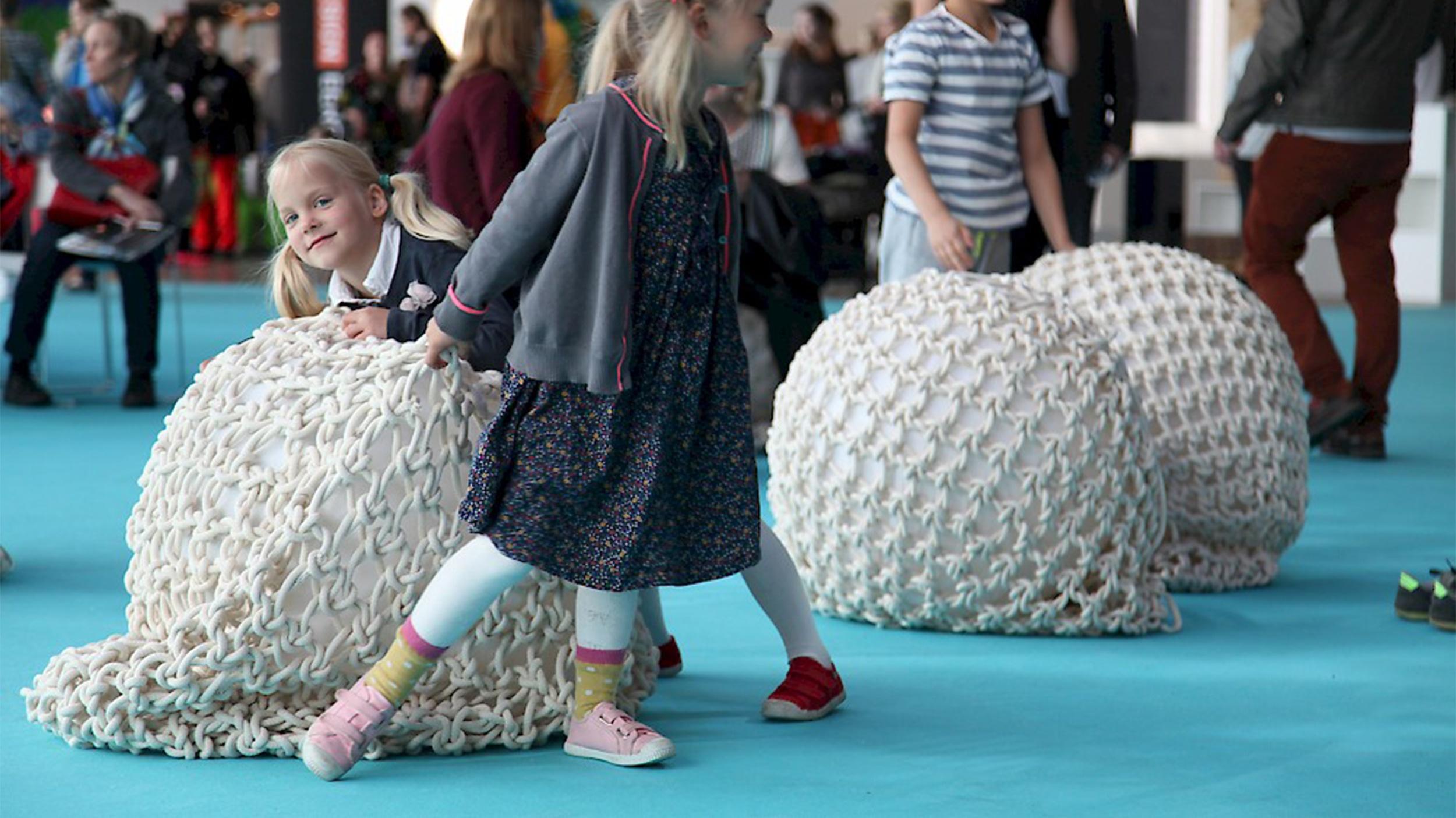 Lapset kiinnostuivat Habitaren sateenvarjoinstallaatioon kuuluvista tyynyistä.