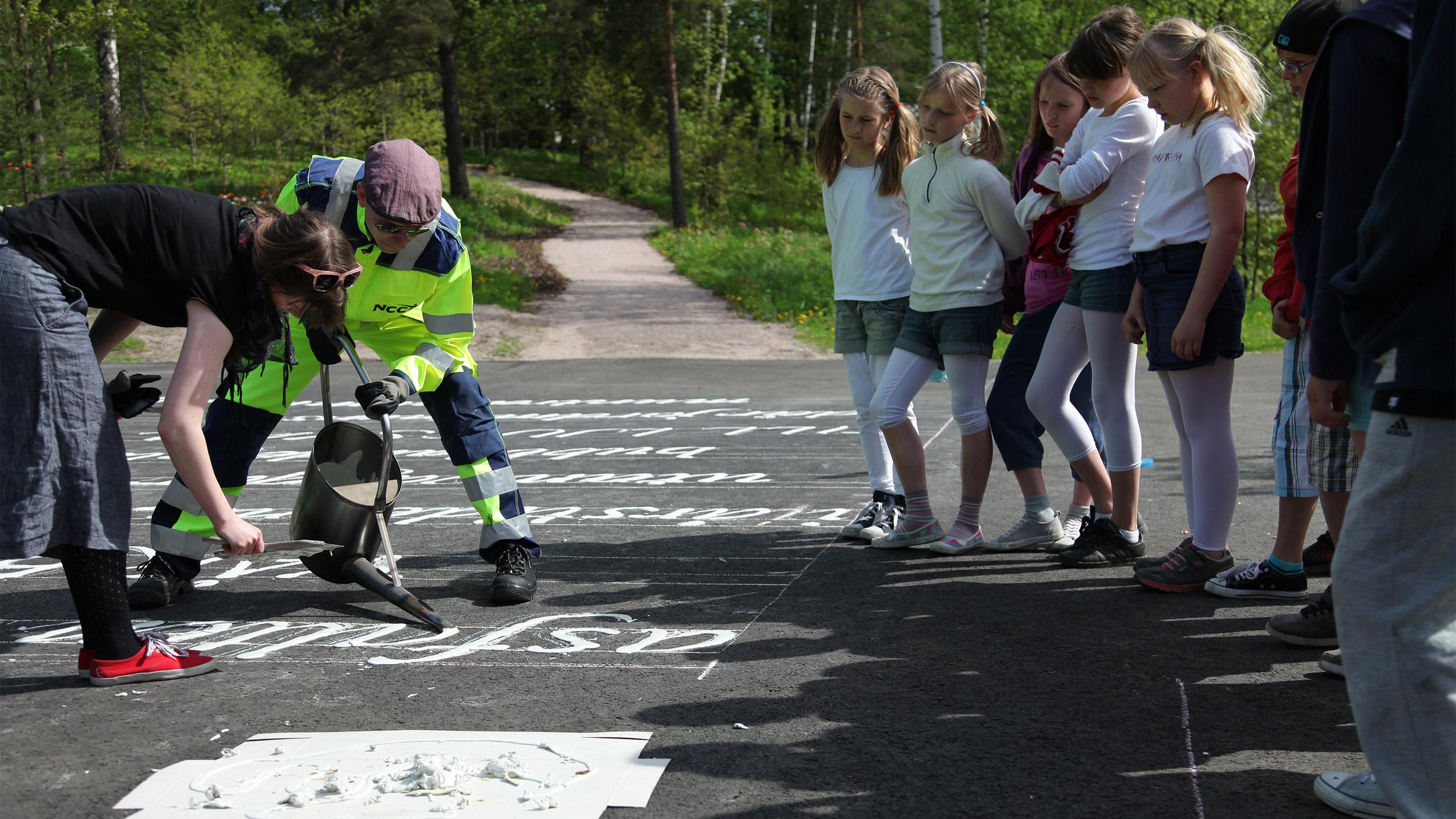 Runoja maalataan asfalttiin Kauniaisissa Rytmi-teosta varten